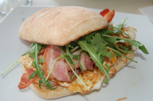 Panini with fried egg, bacon, onion jam, rocket and aioli