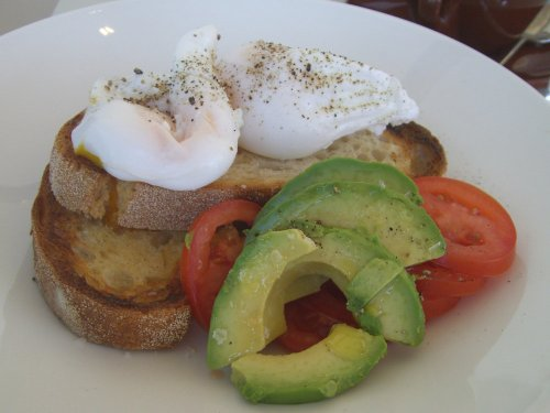 Poached eggs on sourdough with sides of avocado and tomato